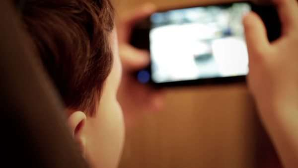 Teenager is playing his portable game console. Focus is on the boy. Console is washed out. Royalty-free stock video