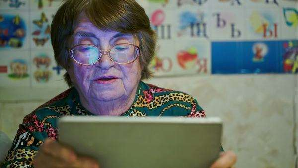 Elderly woman scrolling photos on tablet computer and telling something. Pictures reflecting in her glasses Royalty-free stock video