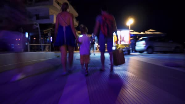 Hyperlapse shot of family walking along the brightly lit night street in resort town Royalty-free stock video