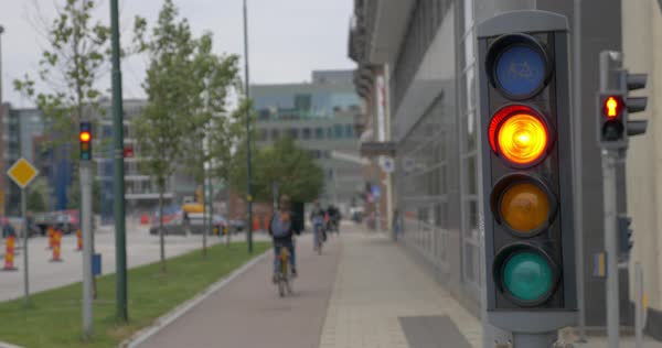 Working traffic lights for bicycles in foreground, people riding bikes in the street in background Royalty-free stock video