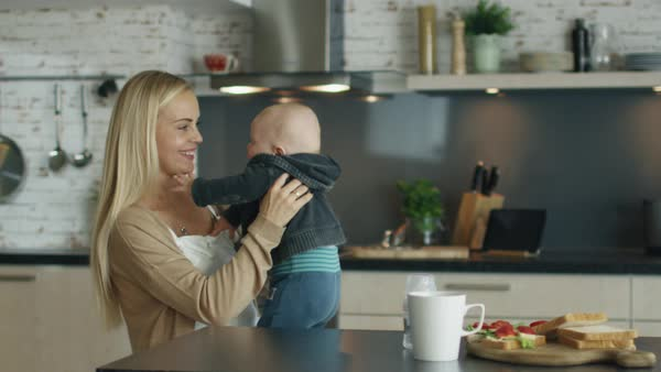 Young mother plays with her beautiful baby while standing in the kitchen Royalty-free stock video