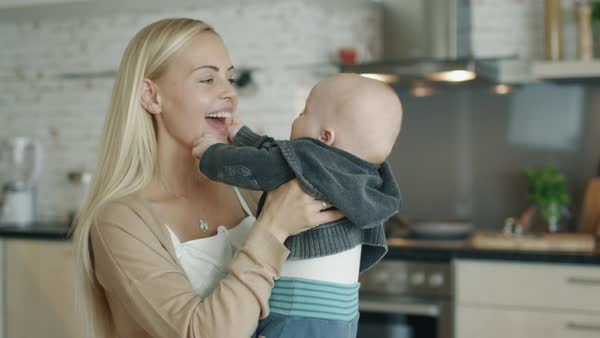 Young mother holds and plays with her baby while standing in the kitchen Royalty-free stock video