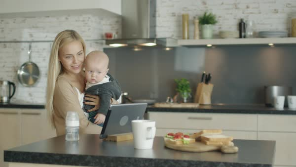 Young mother holds her child and uses tablet computer while being in the kitchen Royalty-free stock video