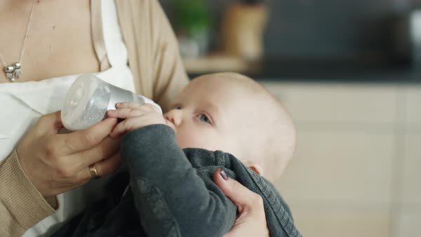 Close-up shot of a mother feeding her gorgeous child from a bottle Royalty-free stock video