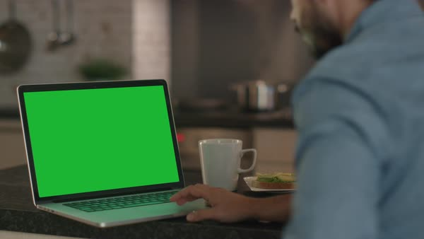 Young man uses laptop with a green screen while sitting at the kitchen table Royalty-free stock video