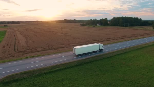 Following and aerial shot of a truck driving on highway. Beautiful field landscape and setting sun is seen. Royalty-free stock video