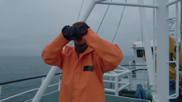 Captain of commercial fishing ship dressed in protective coat looking through binoculars Royalty-free stock video