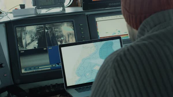 Captain of commercial fishing ship surrounded by monitors and screens working with sea maps in his cabin. Royalty-free stock video