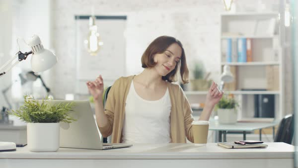 Creative young woman dances while sitting at her workplace desk. she sits in a light and modern office place. Royalty-free stock video