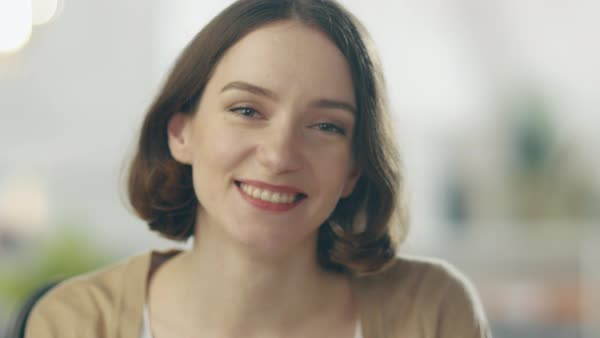 Camera focuses on a beautiful smiling brunette. she is charming. her background is out of focus. Royalty-free stock video
