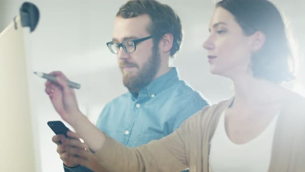 Young man and a woman discuss working process on a whiteboard. man holds smartphone. woman draws on a whiteboard. Royalty-free stock video