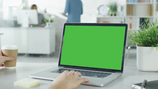 Close-up of a man's hands working on green screen on a laptop. In background blurred and brightly lit office where one man approaches the other and they have discussion. Royalty-free stock video