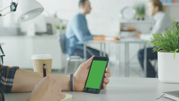 Close-up of a man's hands holding green screen smartphone and making notes with pen. In the background bright modern office with two men having conversation. Royalty-free stock video