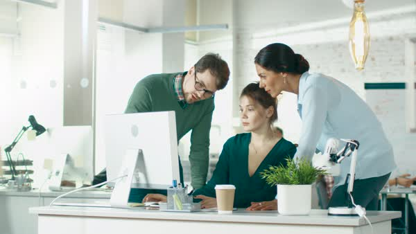 In brightly lit and modern creative bureau. In foreground three people discuss business issues using desktop computer. In background groups of coworkers discuss work related matters. Royalty-free stock video
