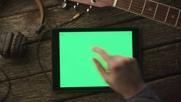Musician using tablet pc with green screen in landscape mode, top view. Royalty-free stock video