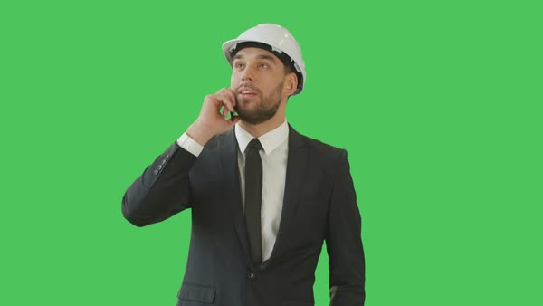 Medium shot of a businessman in a hard hat talking on the phone and waving hello to somebody. Background is green screen. Royalty-free stock video