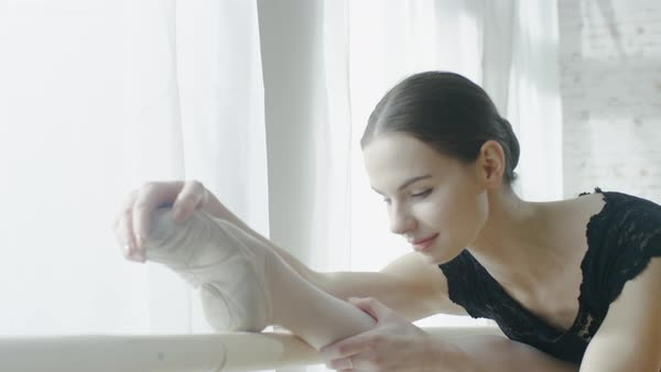 Close-up of a young and beautiful ballerina doing leg stretching at the barre Royalty-free stock video