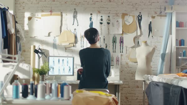 Zoom out of a female fashion designer looking at drawings and sketches that are pinned to the wall behind her desk. Studio is sunny. Personal computer, colorful fabrics, sewing items are visible. Royalty-free stock video