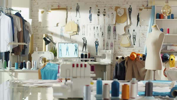 Shot of a sunny fashion design studio. We see working personal computer, hanging clothes, sewing machine and various sewing related items on the table, mannequins standing, colorful fabrics. Royalty-free stock video