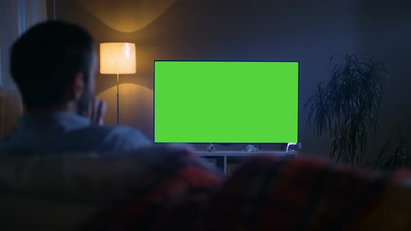 In the evening back view of a middle aged man sitting on a couch watching big flat screen tv Royalty-free stock video