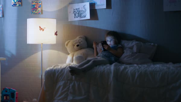 Cute little girl lies on her bed and watches cartoons on a smartphone. Her floor lamp is on. Royalty-free stock video