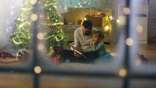 Looking Through the Window. Sitting Under Christmas Tree with Gifts Under It Father Reads Book to His Daughter. Royalty-free stock video