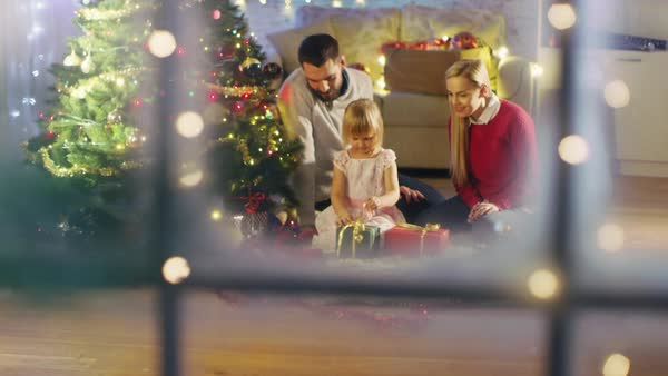 Looking Through Snowy Window. Happy Father, Mother and Daughter Sitting Under Christmas Tree. Daughter Opens Her Presents. Royalty-free stock video