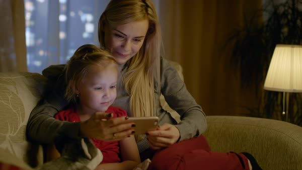 Mother and her cute daughter are sitting on a couch in the living room. They're using smartphone and smiling. It's evening. Royalty-free stock video
