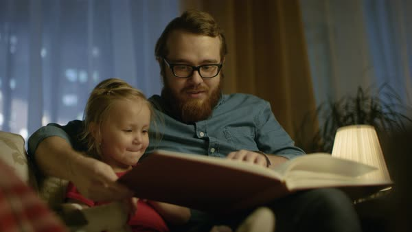 In the evening father and little daughter sitting on a sofa in the living room they are reading children's book. Royalty-free stock video