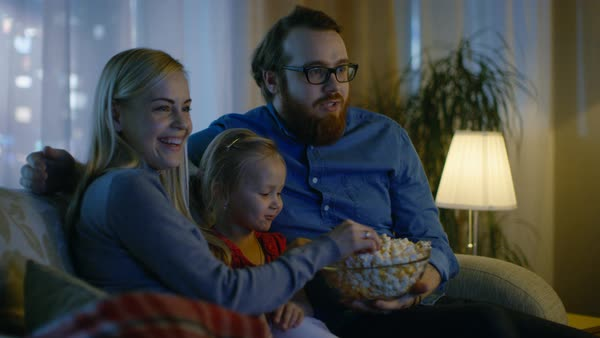 Father, mother and little girl watching tv. They sit on a sofa in their cozy living room and eat popcorn. It's evening. Royalty-free stock video