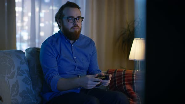 In the evening man is sitting on a sofa and plays in videogames in his living room. Big city is seen behind the windows. Royalty-free stock video