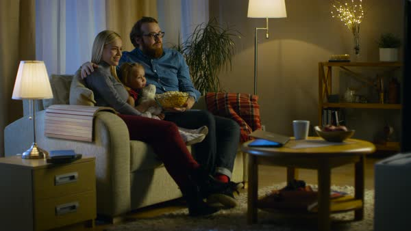 Long shot of a father, mother and little girl watching tv. They sit on a sofa in their cozy living room and eat popcorn. It's evening. Royalty-free stock video