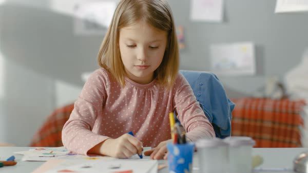 Cute little girl draws with crayons in her light room. Royalty-free stock video