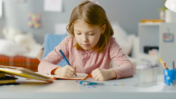 Diligent young girl does homework while sitting in her room. Royalty-free stock video