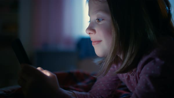 Cute little girl in her room at night, lies on a bed uses smartphone. Screen illuminates her face. Royalty-free stock video