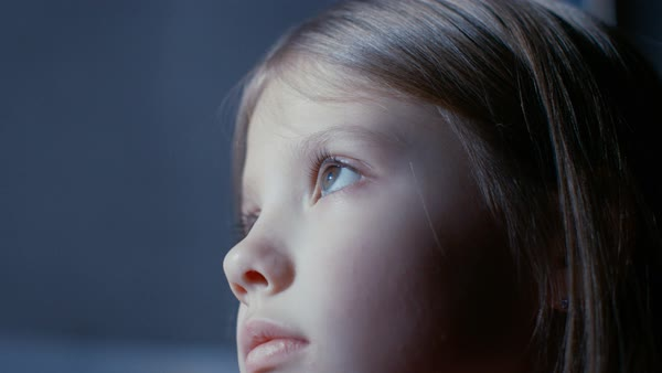 Close-up of a cute young girls face while she's looking at something that illuminates her face. Royalty-free stock video