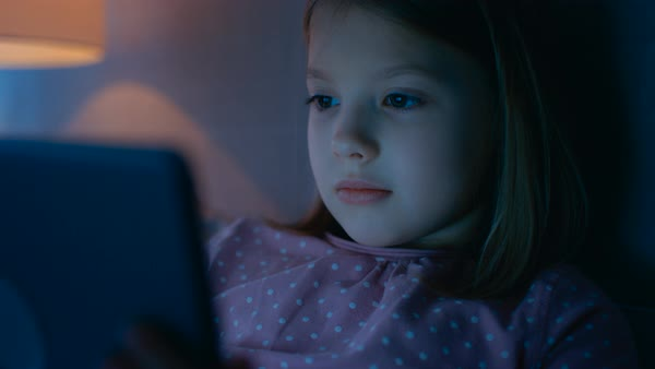 Close-up of a cute young girls face while she's looking at tablet computer that illuminates her face. Royalty-free stock video