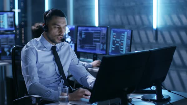 In system control center technical support specialist speaks into headse while sitting at his desk before multiple monitors Royalty-free stock video