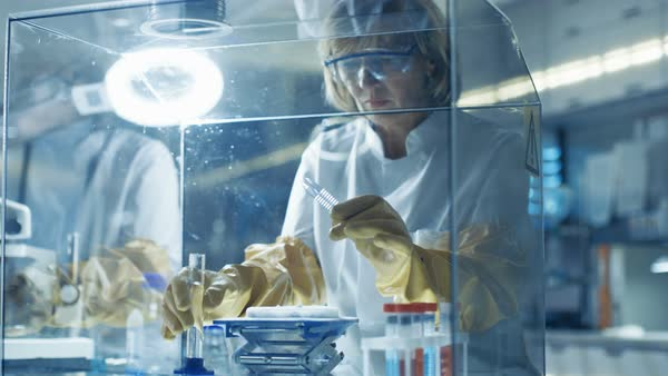 Senior female scientist works with samples in isolation glove box Royalty-free stock video
