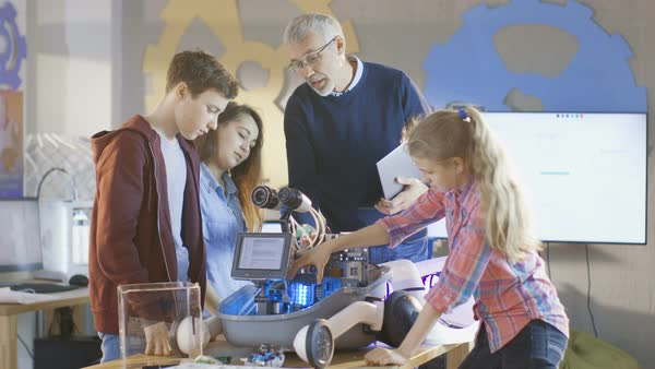 Teacher and his pupils work on a programable robot with led illumination for school science class project Royalty-free stock video