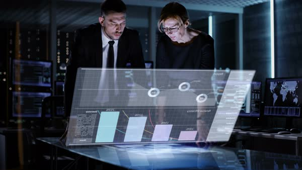 Male and female business managers use touchscreen interactive 3d panel in big monitoring room full of computers with animated screens Royalty-free stock video