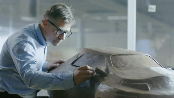 Chief automotive designer with rake sculpts futuristic car model from plasticine clay. He works in a special studio located in a large car factory. Royalty-free stock video