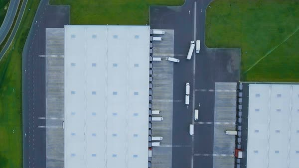 Zoom in aerial shot of industrial warehouse/ storage building/ loading area where many trucks are loading/ unloading merchandise Royalty-free stock video