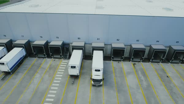 Moving aerial side shot of industrial warehouse loading dock where many truck with semi trailers load/ unload merchandise Royalty-free stock video
