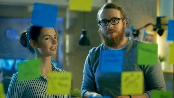 Male and female designers plan their next project on a glass wall with sticky notes outline Royalty-free stock video