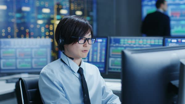 In the Network Operations Center Trader Makes Personal Client Call with a Headset. He's Surrounded by Monitors Showing Stocks Data and Graphs.  Royalty-free stock video