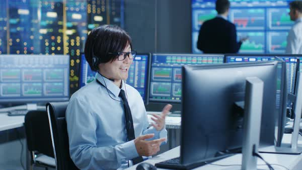 In the Network Operations Center Trader Makes Personal Client Call with a Headset. In the Background Traders Discuss Data Shown on Monitors.  Royalty-free stock video