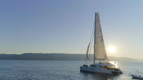 Aerial Shot of a Sailing Catamaran Yacht with Raised Sail Traveling Through The Calm Seas with Sun Rising Behind the Hills. People Relaxing on the Deck. Royalty-free stock video