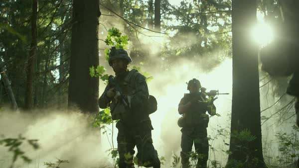 Fully equipped soldiers wearing camouflage uniform attacking enemy, rifles ready to shoot. Military operation in action, squad running in formation through dense smokey forest.  Royalty-free stock video