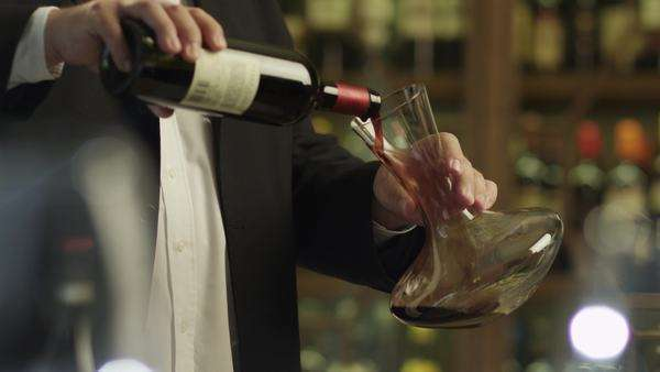 Sommelier pouring red wine into decanter being in restaurant. Royalty-free stock video